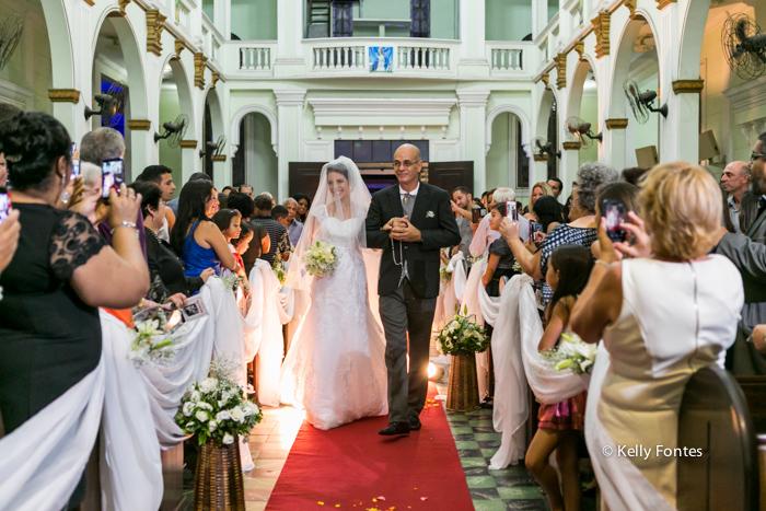 Foto casamento rj noiva entrando com o pai na Igreja nave corredor até altar convidados nos bancos com celular fotografando por kelly fontes fotografia