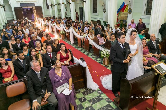 Foto casamento rj noiva e noivo com padre no altar Igreja lotada de convidados e parentes noivos por kelly fontes fotografia