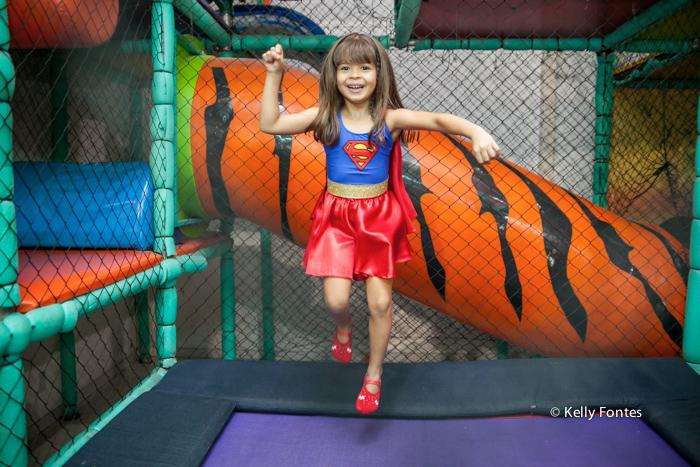 fotos festa infantil rj - bolo mulher maravilha super heróis menina Luisa sorrindo e pulando no brinquedo pula