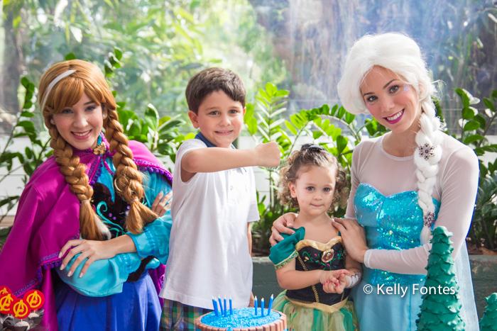 Fotografia festa infantil RJ - Os Vingadores e Frozen - Foto de criança na mesa do bolo com as princesas Elsa e Anna, Na Moitta Itanhangá RJ