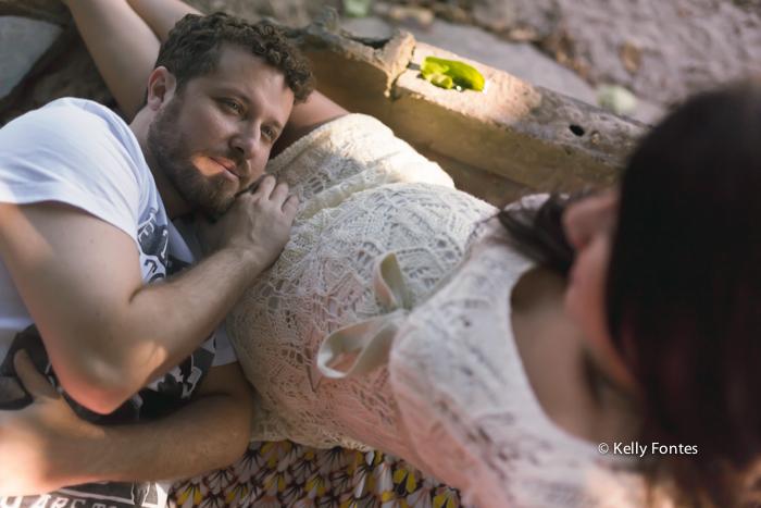 book gestante com marido nas pedras da praia RJ fotografia pai deitado na coxa da esposa pôr do sol grávida