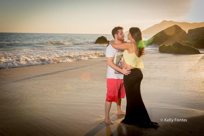 book gestante na areia da praia RJ fotografia pôr do sol grávida com o marido abraço na água do mar