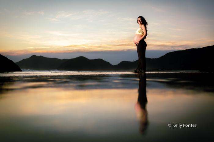book gestante na areia da praia RJ Dani grávida do Bruno reflexo do sol na água do mar