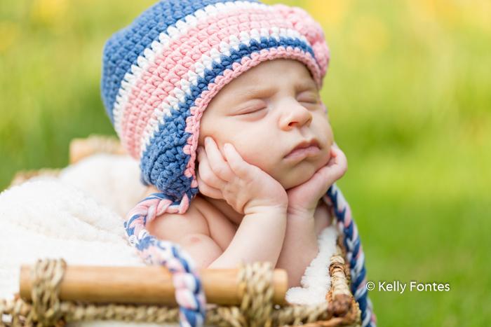 Fotografia Newborn RJ Recém Nascido Bebê com touca azul com tranças flor rosa segurando cabeça sobre as mãos dentro cestinha por Kelly Fontes