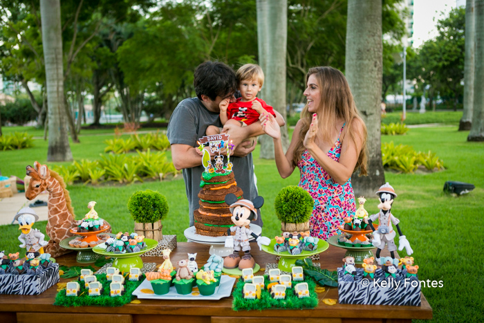 Fotografia Festa Infantil RJ 2 Anos David Safari do Mickey Colo Pai Mãe Palmas Parabéns Safari Mickey Bichinhos Pelúcia Mesa Madeira Marrom Fundo Verde