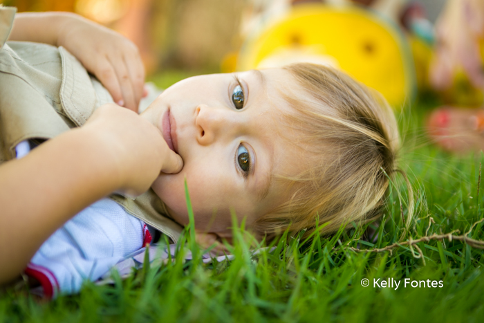 Fotografia Festa Infantil RJ 2 Anos David Safari do Mickey Deitado Grama Dedo Boca Fundo Verde Amarelo